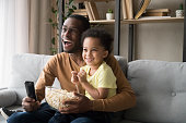 Happy African American father with son watching tv, eating popcorn