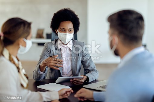 Happy black bank manager with face mask using touchpad while talking to her clients on a meeting in the office.