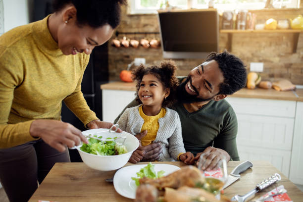 Happy African American girl having Thanksgiving lunch with her parents at dining table. stock photo
