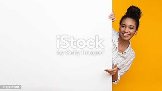istock Happy African American Girl Looking Out Behind Blank Advertisement Board 1209053082