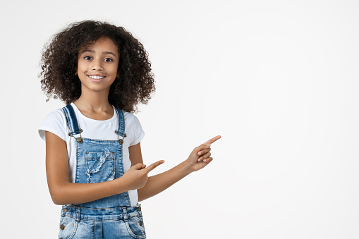 Happy african american girl pointing fingers aside at copy space isolated over white background