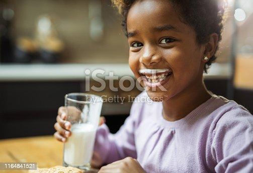 Happy black girl having yogurt mustache at home and looking at camera.