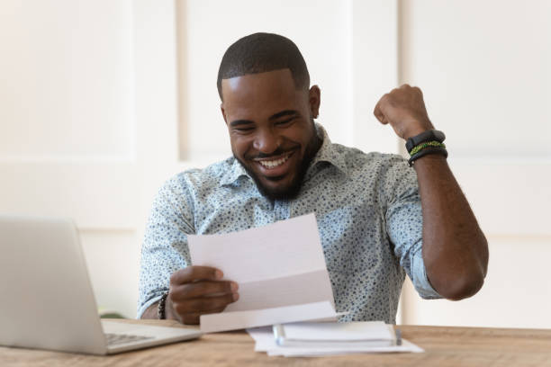 Happy african american guy received banking loan approval. Happy euphoric young african american guy received paper report, university admission letter, celebrating important goal achievement, banking loan approval, full credit repayment, lottery win notice. refund stock pictures, royalty-free photos & images