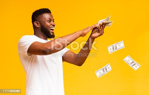 istock Happy african american guy throwing out money banknotes 1171063080