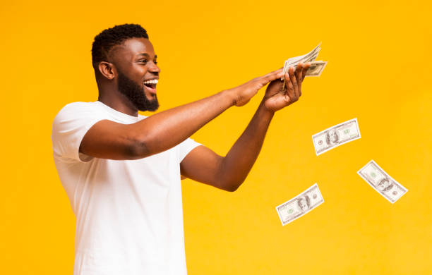 happy african american guy throwing out money banknotes - throw money away stock pictures, royalty-free photos & images