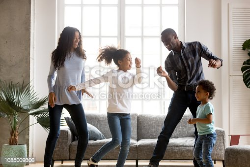 Happy African American having fun together indoors, funny married couple dancing with adorable little preschooler daughter and cute toddler son at home, listening to music, family weekend with kids