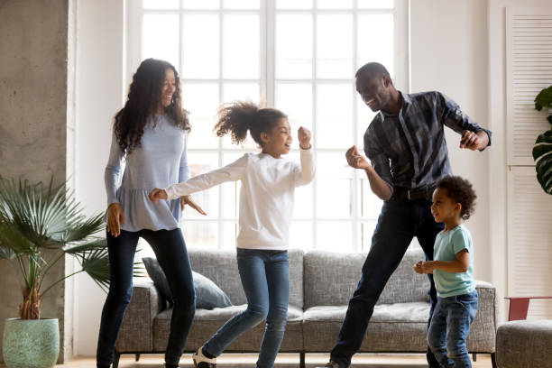 Happy African American having fun together indoors Happy African American having fun together indoors, funny married couple dancing with adorable little preschooler daughter and cute toddler son at home, listening to music, family weekend with kids dancing stock pictures, royalty-free photos & images