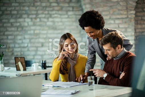 istock Happy African American insurance agent and couple going through savings plans. 1136559209