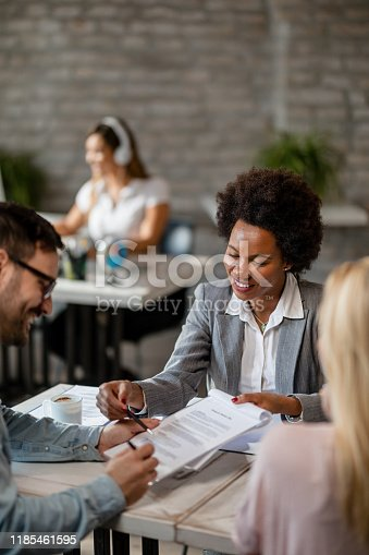 944314580 istock photo Happy African American insurance agent showing to a couple where to sign the contract. 1185461595