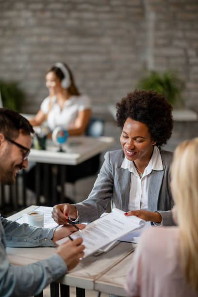 happy african american insurance agent showing to a couple where to sign the contract. - mortgages and loans stock pictures, royalty-free photos & images