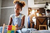 Cute african girl playing with counting frame at home