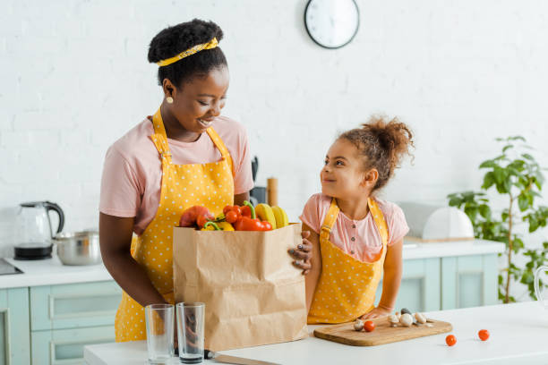 happy african american kid looking at mother near groceries - grocery home foto e immagini stock