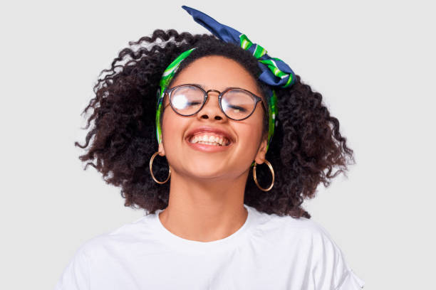 Happy African American lady smiling broadly, wearing white t shirt and transparent eyewear, enjoy good time, posing against white studio background. People, success, emotions and happiness concept stock photo