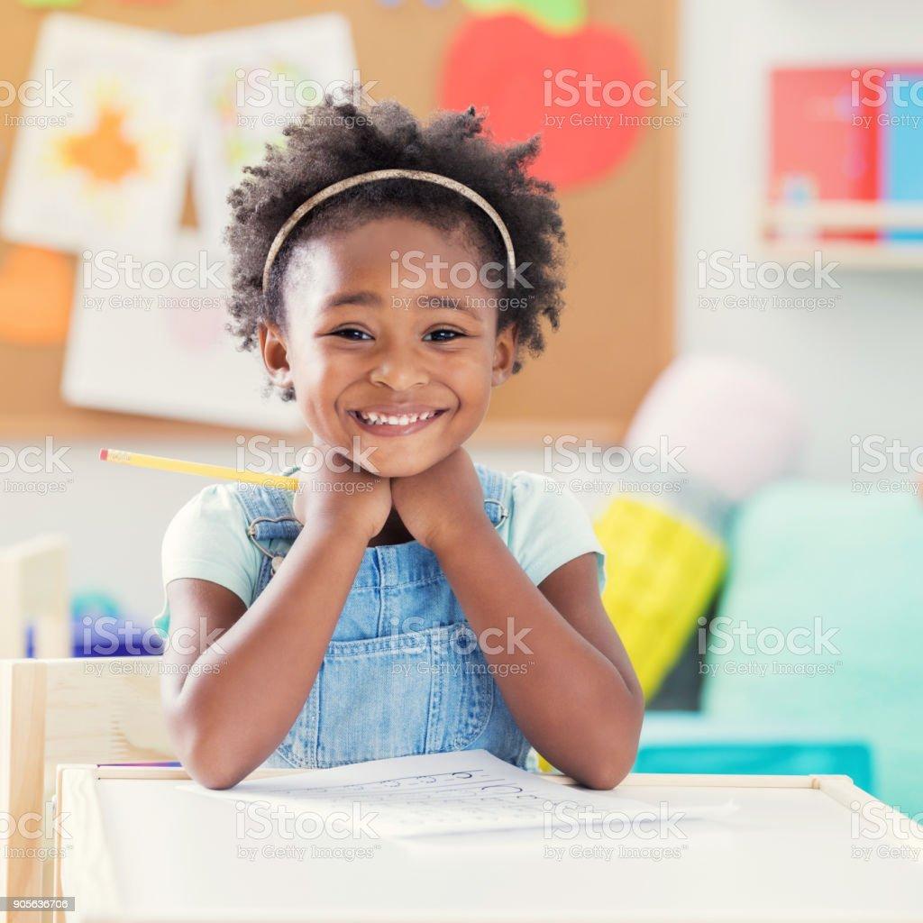 Happy African American little girl enjoys preschool stock photo