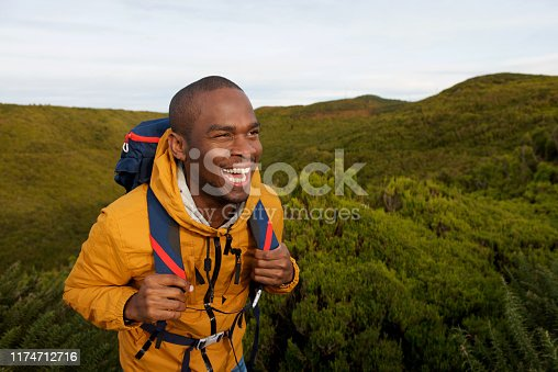 Portrait of happy african american male backpacker walking in nature
