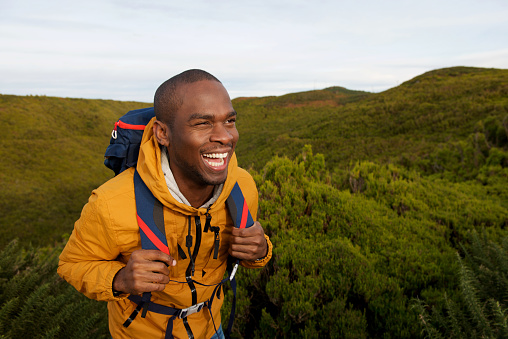 Portrait of happy african american male backpacker walking in nature