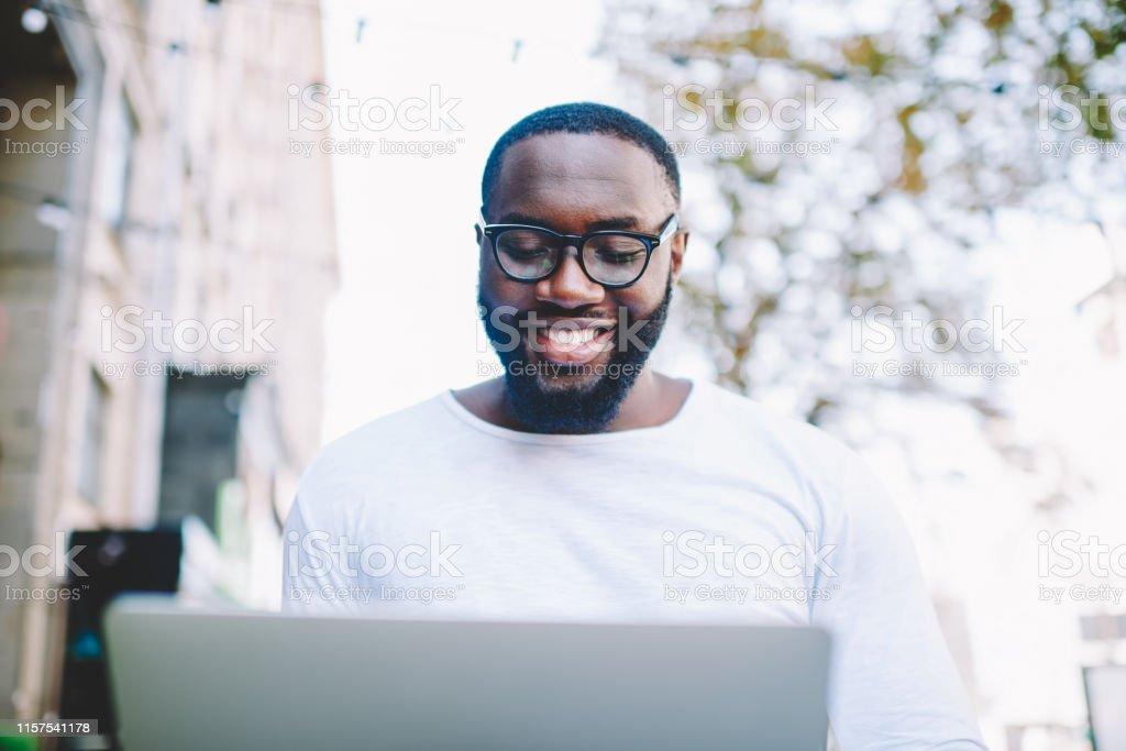 Happy African american male freelancer enjoying remote job outdoors...