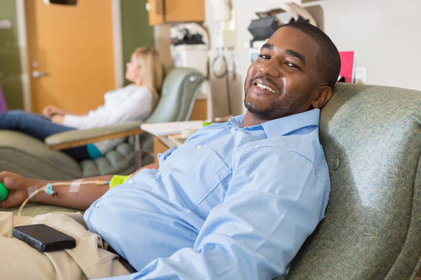 Happy African American man donating blood in hospital lab stock photo