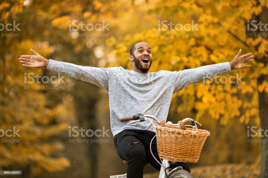 Happy African American man having fun while cycling with his arms outstretched in autumn day. stock photo