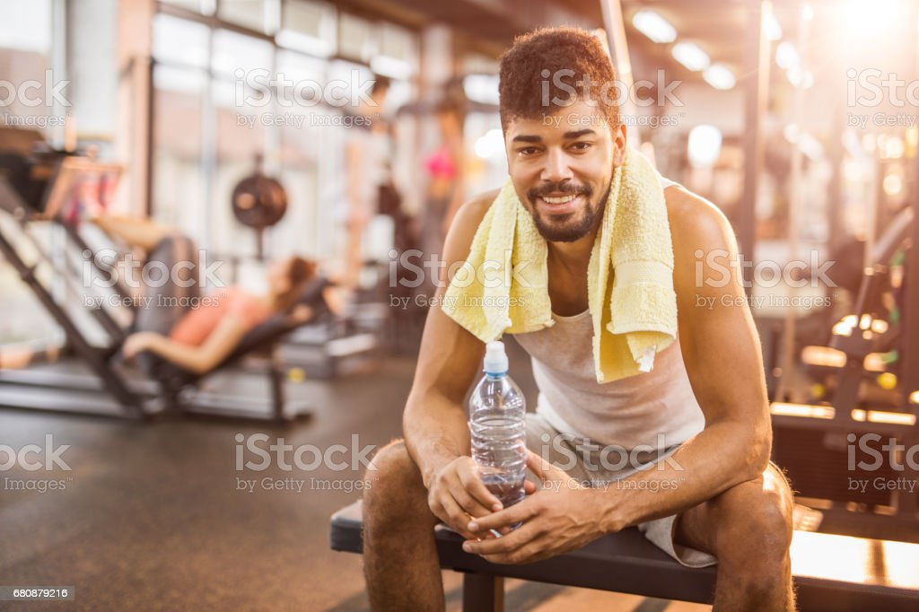 Happy African American man on a water break at gym. stock photo