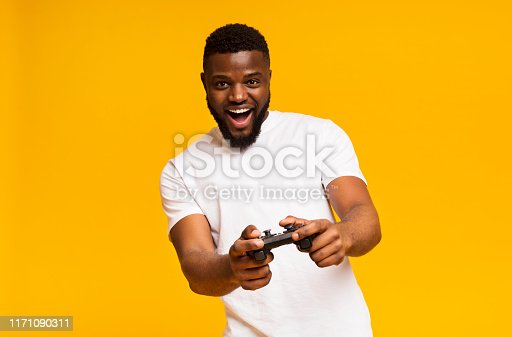 Joyful african american man playing video games with joystick over yellow background, copy space