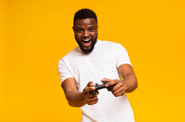 happy african american man playing video games with joystick - man joystick imagens e fotografias de stock