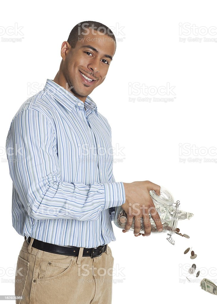 Happy African American man pouring money through jar royalty-free stock photo