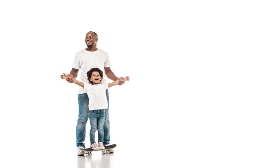 happy african american man supporting cheerful son standing on penny board on white background