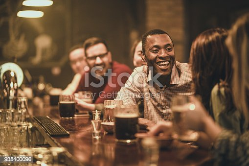 istock Happy African American man talking to his friend during the night out in a pub. 938400096