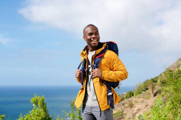 glücklicher afrikanischer amerikanischer Mann mit Rucksack in der Natur – Foto