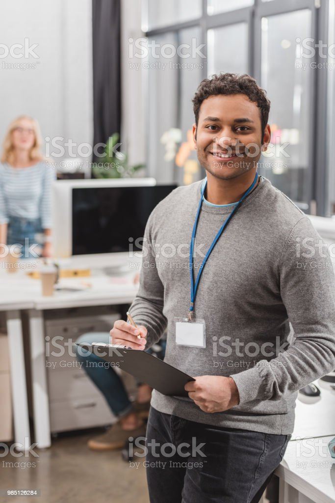 Happy African American Man With Name Tag Writing Something ...