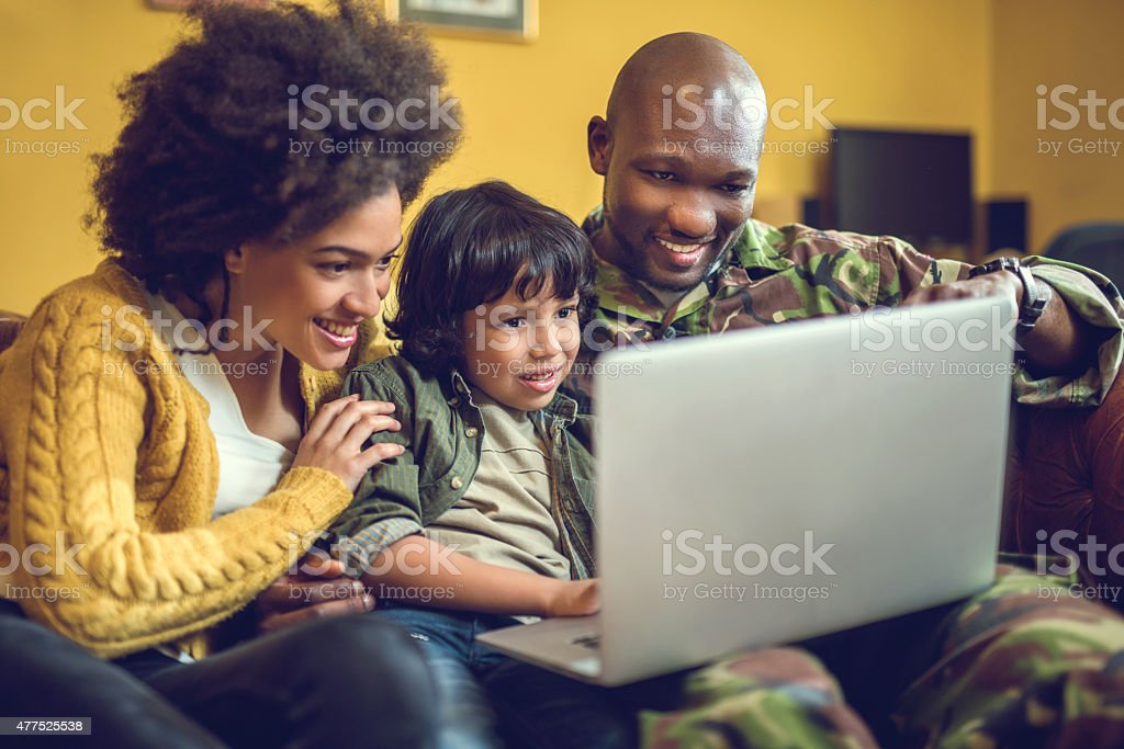 Happy African American military family using laptop at home. stock photo