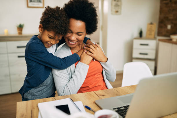 Happy African American mother and son embracing at home. stock photo