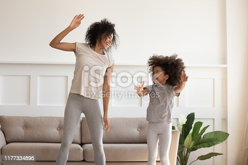 Happy smiling african american mother doing morning exercises with excited little preschooler daughter in stylish living room at home. Overjoyed black family dancing, jumping, having fun together.