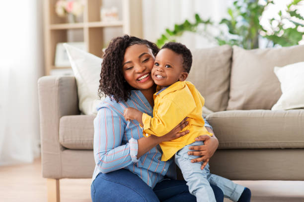 happy african american mother with baby at home stock photo