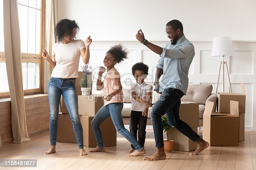 istock Happy african american parents and children dancing celebrating moving day 1158481677