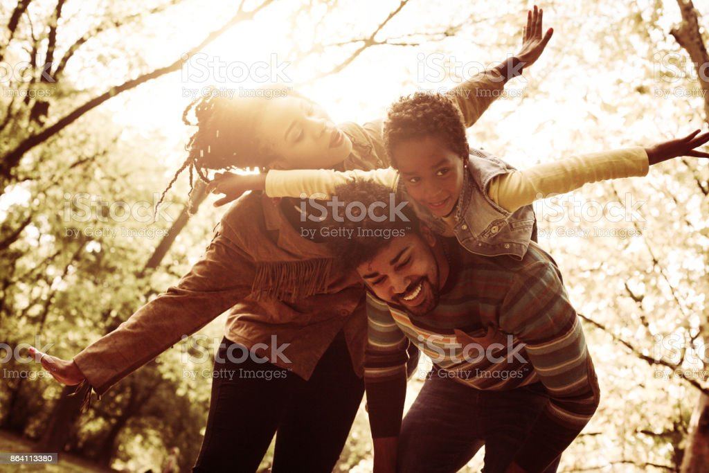 Happy African American parents playing with daughter in nature. royalty-free stock photo