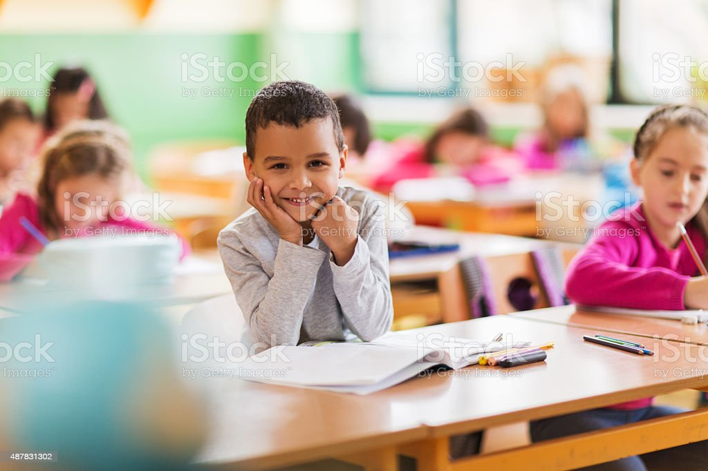 Happy African American schoolboy during a class at school. stock photo