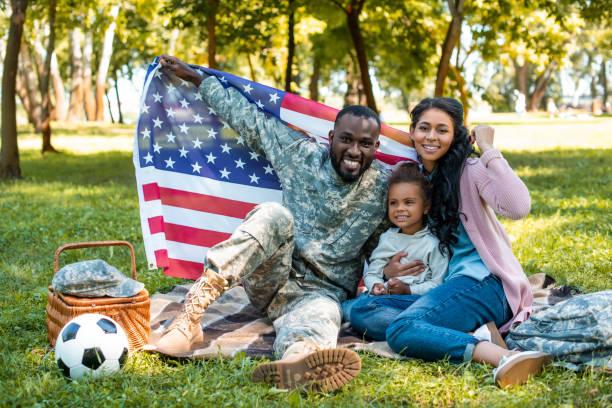 glücklich afroamerikanischen soldaten in militäruniform und familienholding amerikanische flagge im park - camouflagekleidung mädchen stock-fotos und bilder