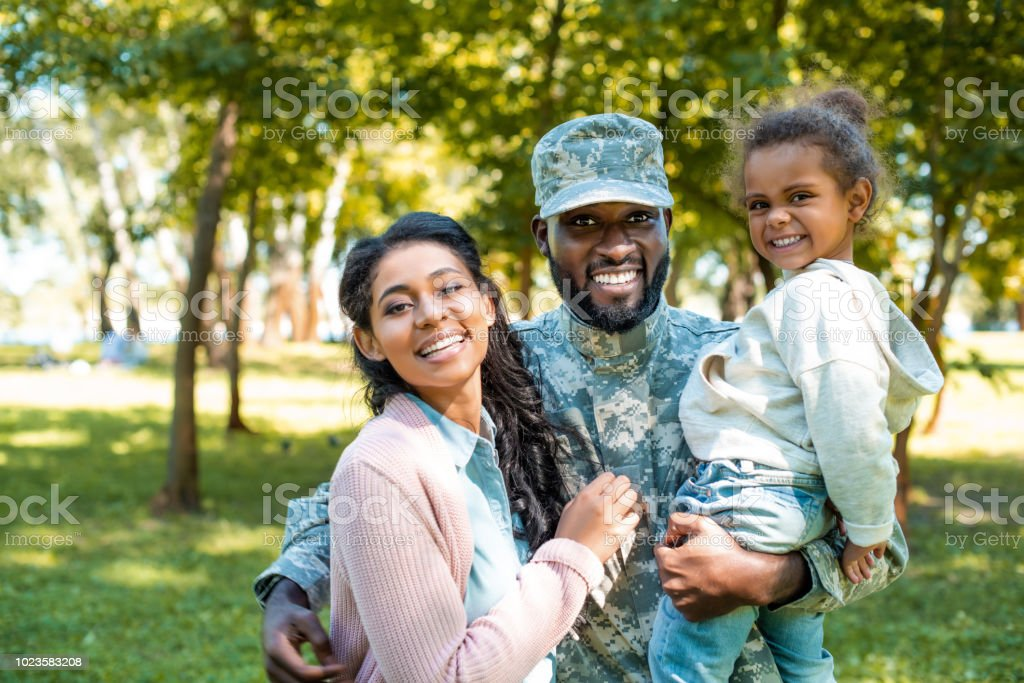 happy african american soldier in military uniform looking at camera with family in park stock photo
