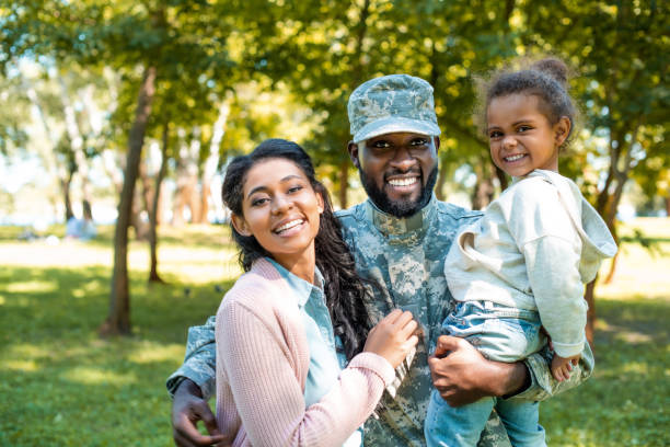 happy african american soldier in military uniform looking at camera with family in park - armed forces stock photos and pictures