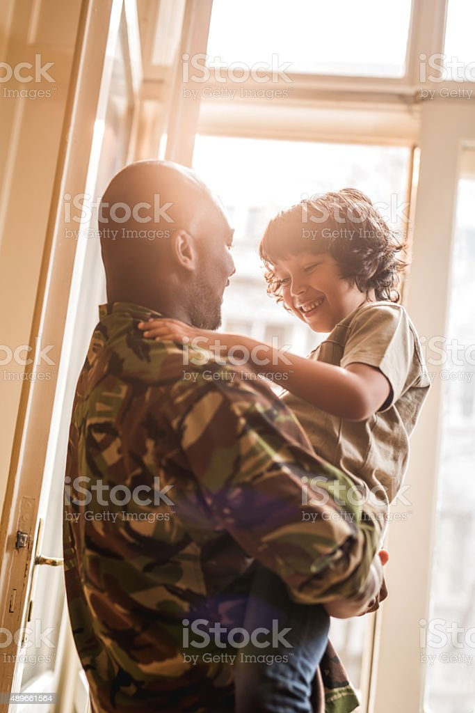 Happy African American soldier talking to his son at home. stock photo