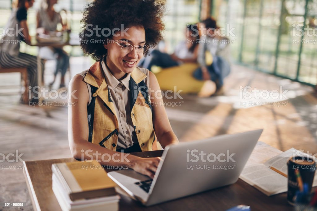 Happy African American student studying while using laptop. - foto stock