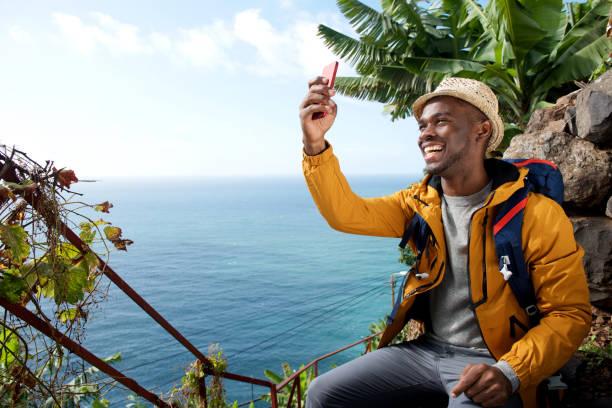 Glücklicher afrikanischer amerikanischer Reisemann nimmt Selfie – Foto