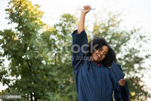 istock Happy African American woman at graduation. 1128584944