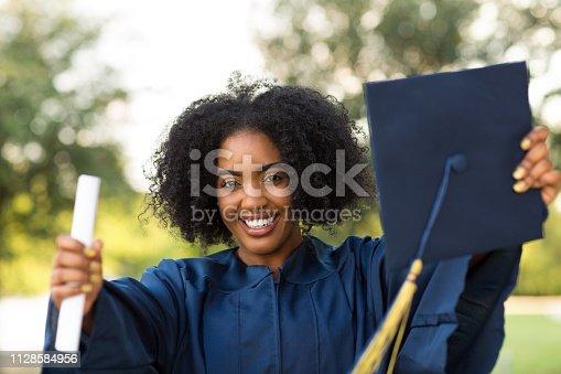 istock Happy African American woman at graduation. 1128584956