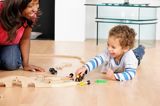 A portrait of a happy African American mother/ childminder/ carer and toddler/ little boy playing a train set  in the living room.