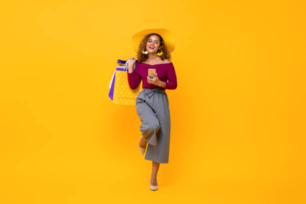 Happy African American woman carrying shopping bags and phone raising one leg stock photo
