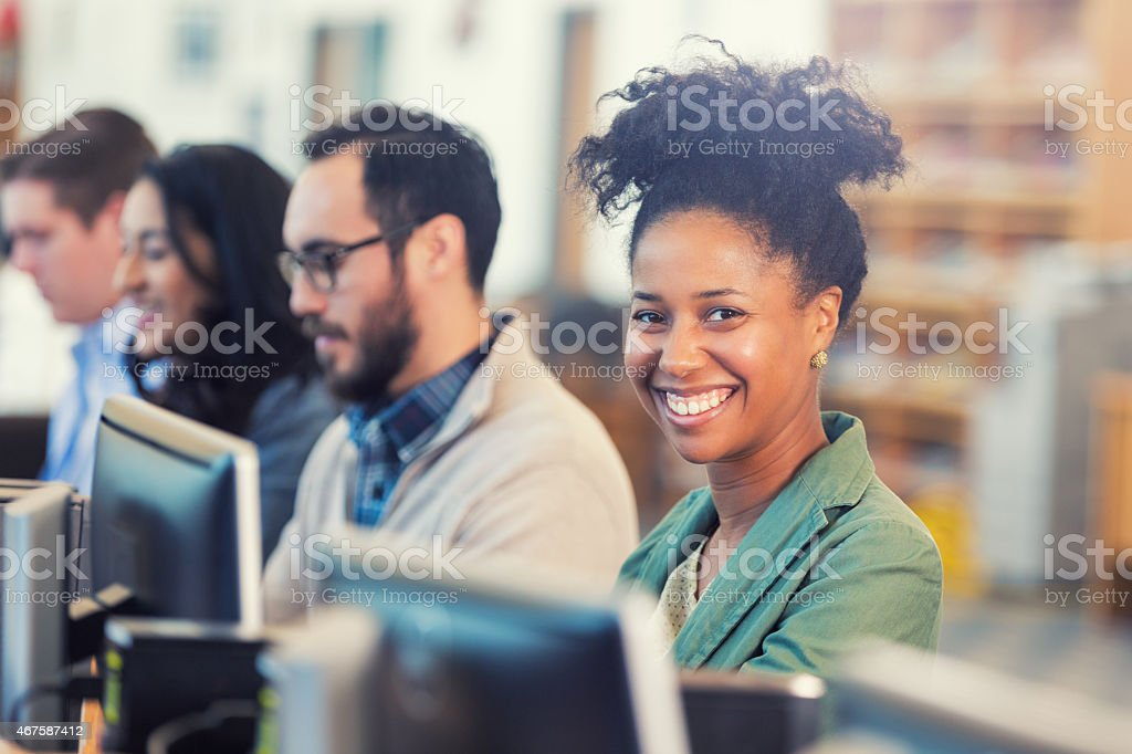 Happy African American woman continuing college education or job training stock photo
