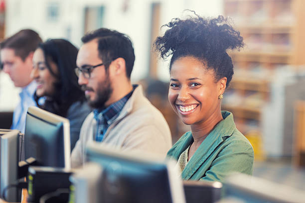 happy african american woman continuing college education or job training - adult education stock pictures, royalty-free photos & images